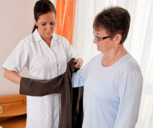 caregiver assisting patient in wearing clothes